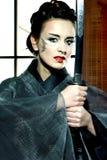 Beautiful japanese kimono woman with samurai sword. Beautiful japanese grey kimono woman with samurai sword in traditional room Stock Photography