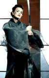 Beautiful japanese kimono woman with samurai sword. Beautiful japanese grey kimono woman with samurai sword in traditional room Royalty Free Stock Photo