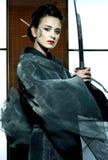 Beautiful japanese kimono woman with samurai sword. Beautiful japanese grey kimono woman with samurai sword in traditional room Royalty Free Stock Image