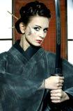 Beautiful japanese kimono woman with samurai sword. Beautiful japanese grey kimono woman with samurai sword in traditional room Stock Photo