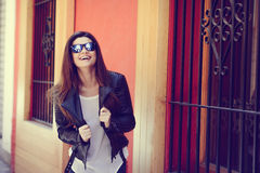Beautiful japanese woman in urban background wearing leather jac. Portrait of beautiful japanese woman laughing in urban background wearing leather jacket Royalty Free Stock Photography