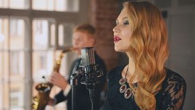 Beautiful jazz vocalist perform on stage with saxophonist. Duet. Live concert. Retro style stock video