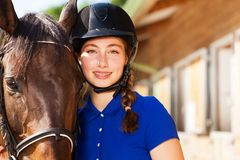 Beautiful jockey girl with her purebred bay horse Stock Image