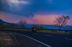 Beautiful Journey... Bike rider enjoying a wonderful motor bike ride during summer thunderstorms in Maharashtra, India Stock Photography