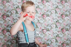Beautiful joyful blond boy blowing soap bubbles. Portrait of funny little boy blowing soap bubbles. Background: floral, soft, pastel Royalty Free Stock Image