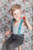 Beautiful joyful blond boy blowing soap bubbles. Portrait of funny little boy blowing soap bubbles. Background: floral, soft, pastel Royalty Free Stock Photography