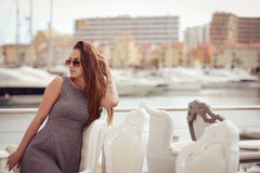 Beautiful joyful female in restaurant on luxury marina background. Royalty Free Stock Photo