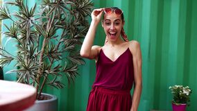 Smiling girl in a burgundy lightweight sundress and pink eyewear posing on green wall background