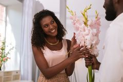 Joyful happy woman taking flowers at home. They are beautiful. Joyful happy women smiling while taking flowers from her husband stock images