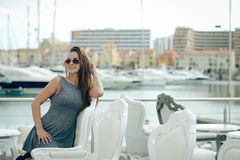 Beautiful joyful smiling female in restaurant on luxury marina background. Stock Images