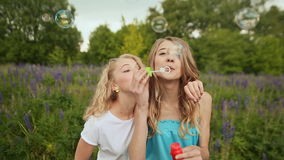 Beautiful joyful teenagers laughing and blowing soap bubbles in spring park. Girlfriends outdoor. Friendship stock video