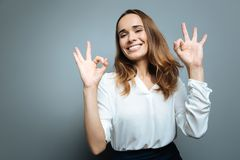Beautiful joyful woman feeling happy. Everything is perfect. Beautiful joyful young woman showing OK gestures and feeling happy while standing against grey Stock Images