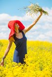Joyful woman in a red hat with a bouquet of wild flowers. Beautiful joyful woman in a red hat with a bouquet of wild flowers in a field with alfalfa Stock Image