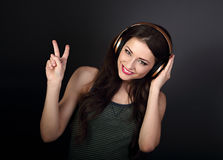 Beautiful joyful young woman listening the music in gold wireles. S headphone and showing victory v-sign gesture by hand on dark grey background Royalty Free Stock Images