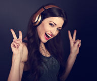 Beautiful joyful young woman listening the music in wireless hea. Dphone and showing victory v-sign gesture by two hands on on dark grey background. Toned Royalty Free Stock Photos