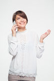 Beautiful joyful young woman standing and talking on cell phone Stock Image