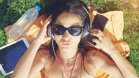 Beautiful joyful young woman in sunglasses lying on the grass, listening to music royalty free stock image