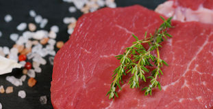 Beautiful juicy fresh meat steak on a table with salt, rosemary, garlic, and tomato on a black background, top view. Concept: fres. H & natural products, bio Stock Photography