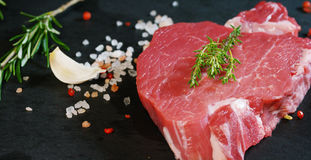 Beautiful juicy fresh meat steak on a table with salt, rosemary, garlic, and tomato on a black background, top view. Concept: fres. H & natural products, bio Royalty Free Stock Photo