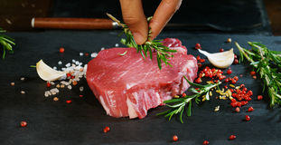 Beautiful juicy fresh meat steak on a table with salt, rosemary, garlic, and tomato on a black background, top view. Concept: fres. H & natural products, bio Royalty Free Stock Images