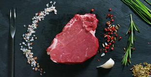 Beautiful juicy fresh meat steak on a table with salt, rosemary, garlic, and tomato on a black background, top view. Concept: fres. H & natural products, bio Royalty Free Stock Image