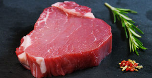 Beautiful juicy fresh meat steak on a table with salt, rosemary, garlic, and tomato on a black background, top view. Concept: fres. H & natural products, bio Stock Image
