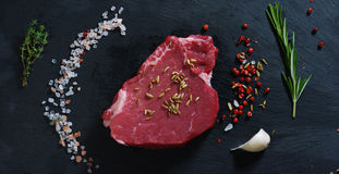 Beautiful juicy fresh meat steak on a table with salt, rosemary, garlic, and tomato on a black background, top view. Concept: fres. H & natural products, bio Stock Photos