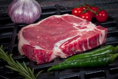 Beautiful and juicy raw steak on the table with ingredients ready to roast royalty free stock image