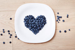 Beautiful juicy ripe natural organic raspberries blackberries blueberries and mint blue tablecloth dots white dish heart shape hea Royalty Free Stock Photo