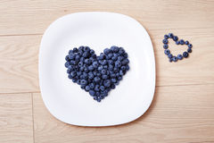 Beautiful juicy ripe natural organic raspberries blackberries blueberries and mint blue tablecloth dots white dish heart shape hea Stock Images