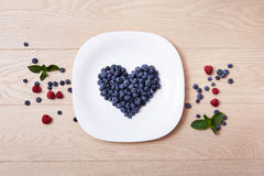 Beautiful juicy ripe natural organic raspberries blackberries blueberries and mint blue tablecloth dots white dish heart shape hea Stock Photos