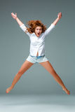 Beautiful jumping girl isolated on blue background Royalty Free Stock Photo