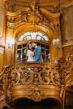 Beautiful just married couple embracing on amazing old stairs with the background of royal wooden vintage interior Stock Image