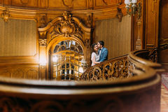 Beautiful just married pair walking up by antique stairs with the background of royal wooden vintage interior Stock Image