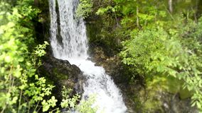 Beautiful 4k steady wild nature landscape shot of small river waterfall running in green tree mountain cliff forest stock video footage