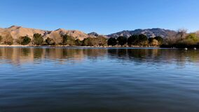 Lake Park with desert mountain view background. Beautiful 4K timelapse pan of lake with desert mountain view background. Video filmed at Hesperia Lake Park stock video