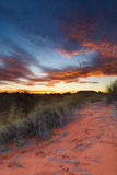 Beautiful kalahari sunset with dramatic clouds and grass Stock Photos