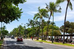 The beautiful Kalakaua Avenue lined with palm coconut trees and. The beach in Waikiki Beach Honolulu Hawaii on the 5th of October 2018 royalty free stock photo