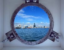 Beautiful Kaohsiung Port Seen Through a Porthole of a Ship. Porthole view of Kaohsiung Harbor and skyline on a bright summer day Stock Image