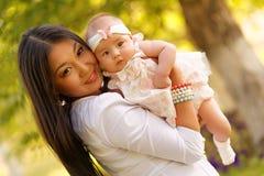 Beautiful kazakh young woman with kids. Beautiful kazakh young women with kids in the park Royalty Free Stock Photography