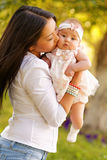 Beautiful kazakh young woman with kids. Beautiful kazakh young women with kids in the park Stock Photo
