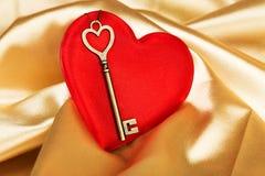 Beautiful key lying on silk heart Royalty Free Stock Photo