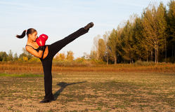 Beautiful kick boxing girl exercising high kick. In the nature on sunny summer day Royalty Free Stock Image