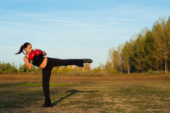 Beautiful kick boxing girl exercising kick in the nature. On sunny summer day Stock Photography