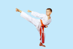 Beautiful kick foot performed by a boy with orange belt Stock Photos