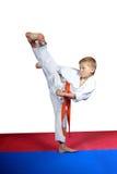 Beautiful kick yoko-geri makes an athlete on a white background Stock Photography