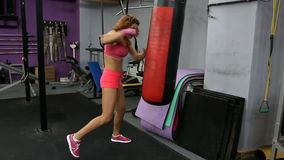 Beautiful Kickboxing woman training punching bag in fitness gym.  stock footage