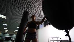 Beautiful Kickboxing woman training punching bag in fitness studio fierce strength fit body kickboxer series.  stock video footage