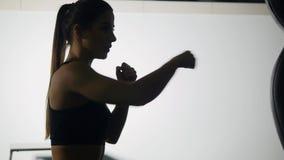 Beautiful Kickboxing woman training punching bag in fitness studio fierce strength fit body kickboxer series.  stock video