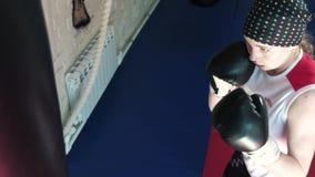 Beautiful Kickboxing woman training punching bag in fitness studio fierce strength fit body kickboxer series 4k stock video footage